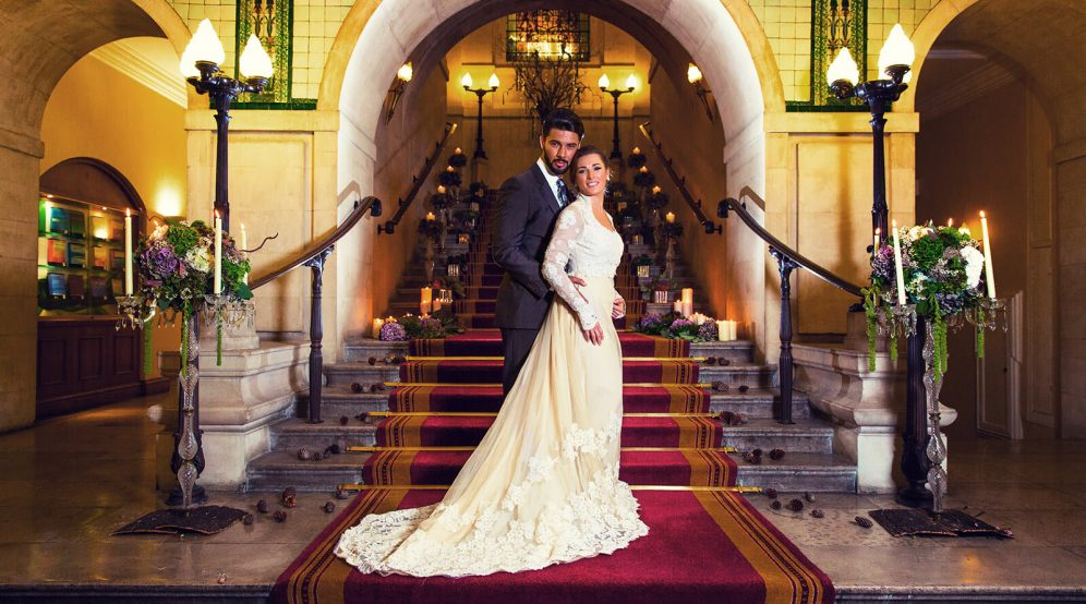 A happy couple striking a pose on 113 Chancery Lane's grand marble staircase.
